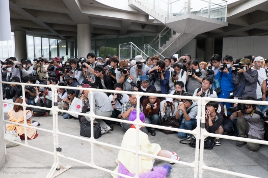 A throng of photographers surrounding cosplayers, some with very low angles.
